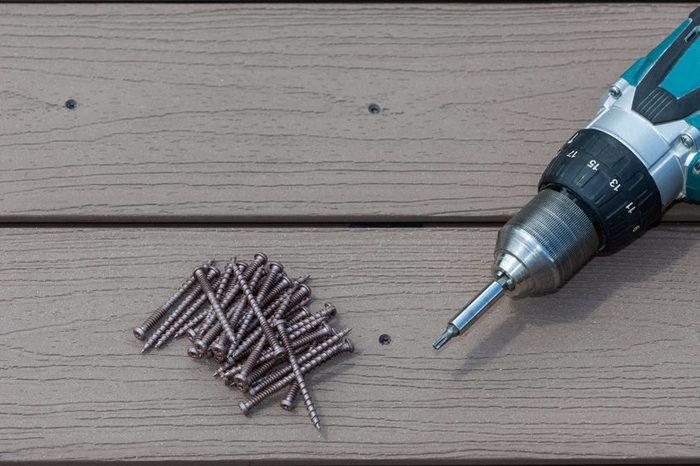 Deck from composite materials. Screw driwer with screws on composite material deck