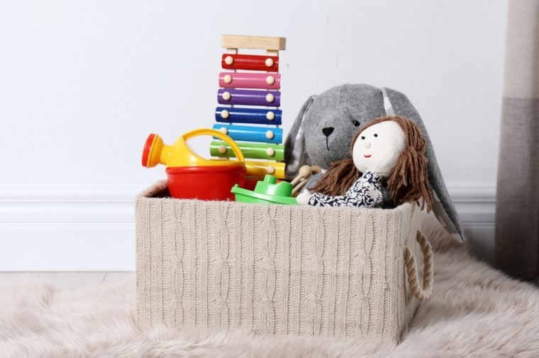 Box with different child toys on floor against white wall. Space for text