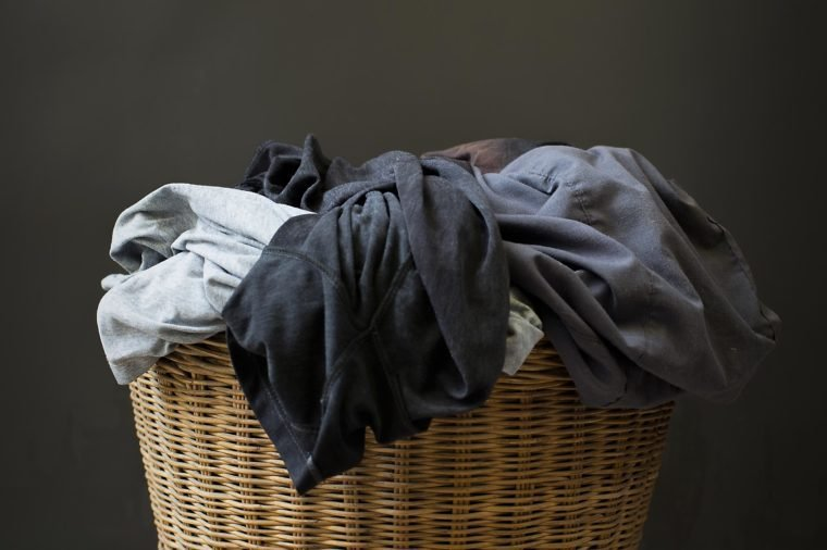 Stack clothes in a basket with a gray background.