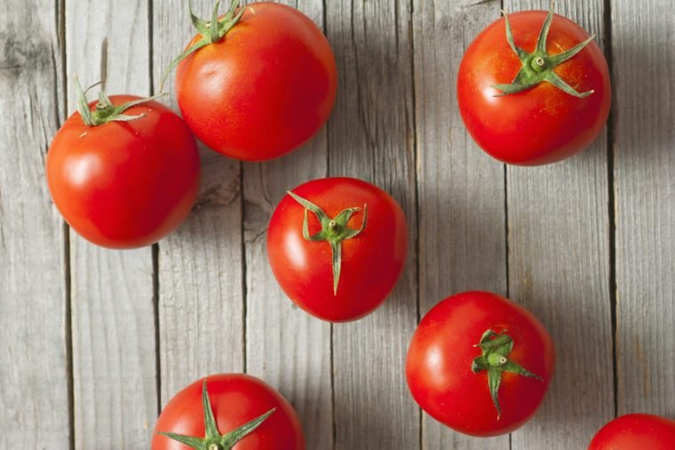 beautiful ripe tomatoes on wood surface