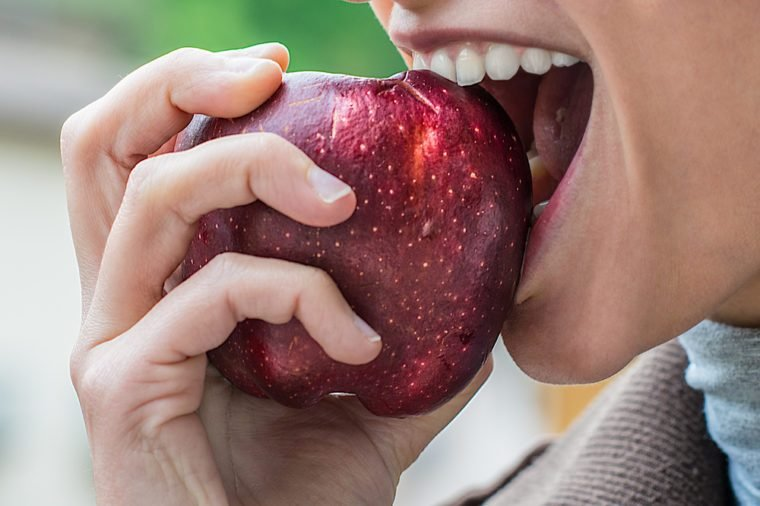 a young attractive girl eats an apple