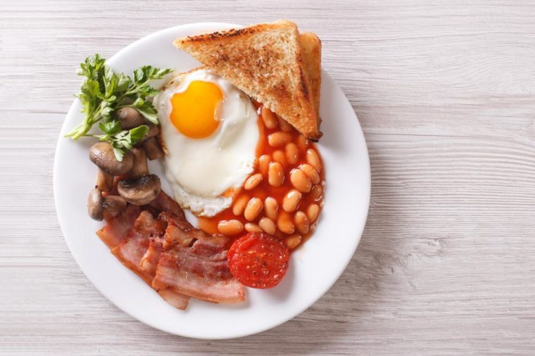 English breakfast: fried egg, bacon, beans and toast on a plate close-up. Vertical view from above