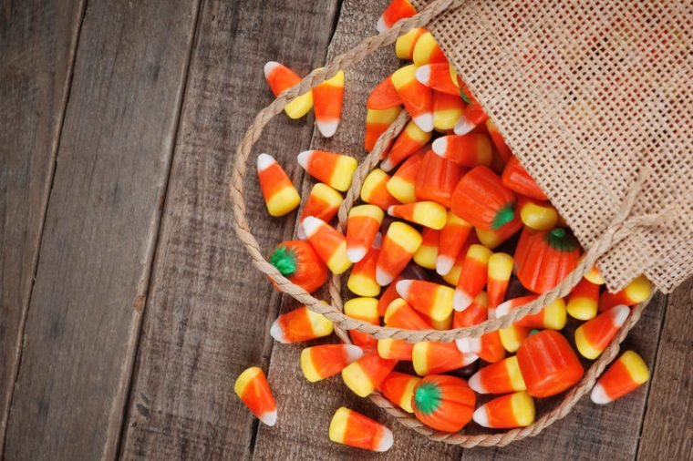 Above view of Halloween candy corn spilling from a burlap bag on rustic wood board background with room or space for copy, text, your words. Horizontal that works vertical with Moody, dark vignette