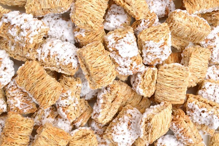 Breakfast setting with frosted wheat cereal on background