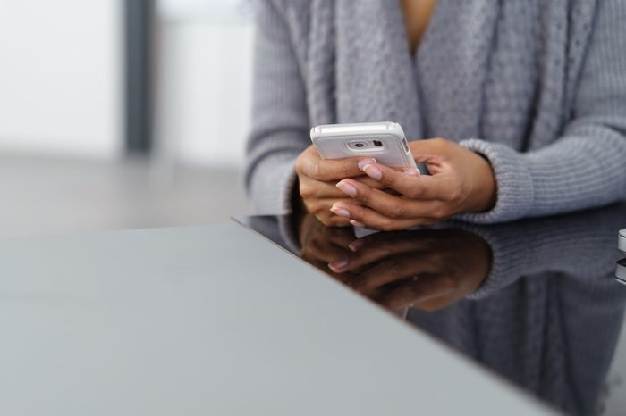 Young African American woman using a mobile phone to send or receive text, close up of her hands seated at a table