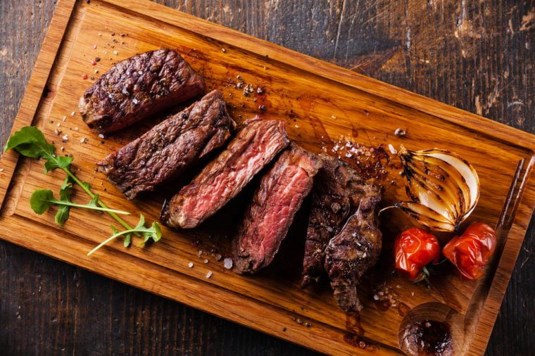 Sliced steak Ribeye with grilled onions and cherry tomatoes on cutting board on wooden background
