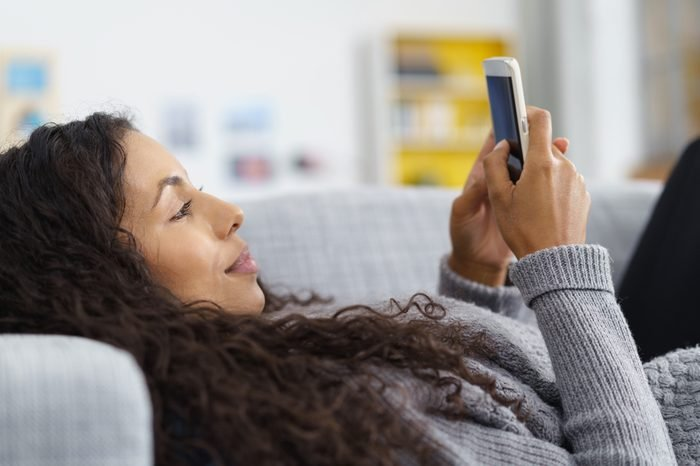 woman lying on the sofa while writing a text message on her cell phone