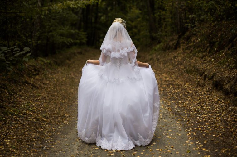 Photo of the bride from the back, wedding dress on a girl, the bride in the forest, the princess in the forest, wedding gown from the back on woman, hem dress, veil, wedding photo shoot, hairstyle