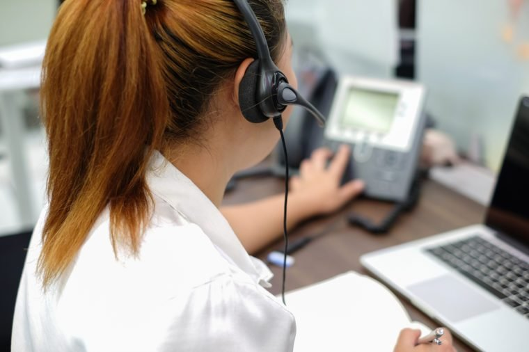 close up focus on headphone of asian call centre response answer or use telephone working in operation room concept.