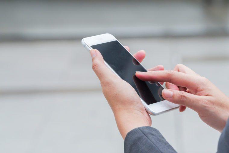 businesswoman using a digital touch smart phone, hands close up