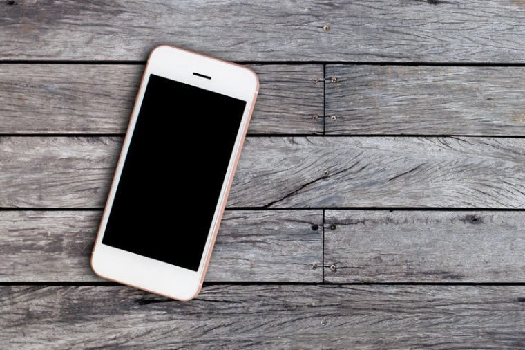 Mobile phone with blank screen on wooden table background with copy space