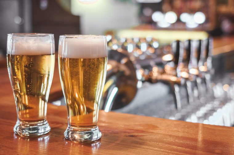 Two Glasses of Beer on a bar table. Beer Tap on background