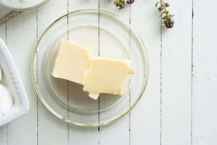 butter on white wooden table background