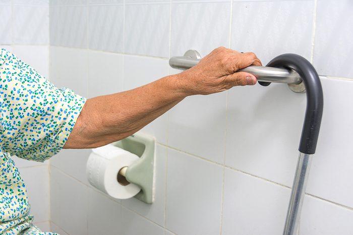 elderly woman holding a grab bars in a bathroom