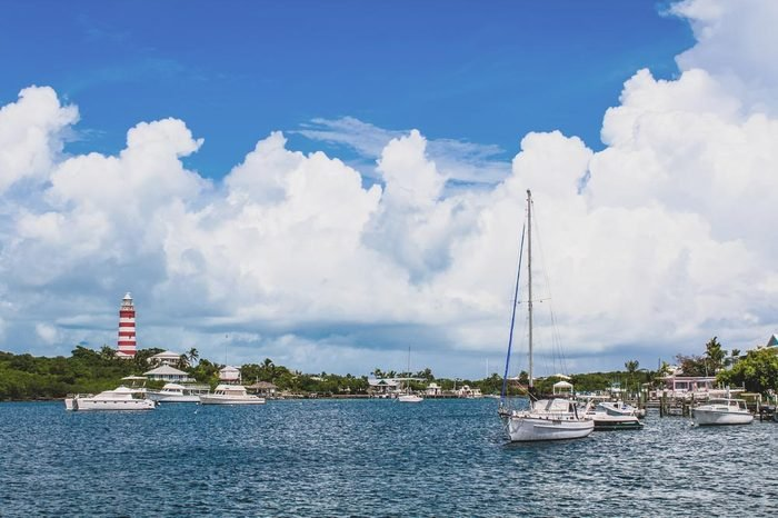 View of Hope Town harbour with lighthouse, sailboat and beautiful sky on a sunny day. Hope Town, Elbow Cay, Abaco, Bahamas