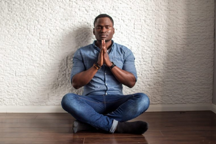 Relaxed handsome african young man sitting and meditating on office