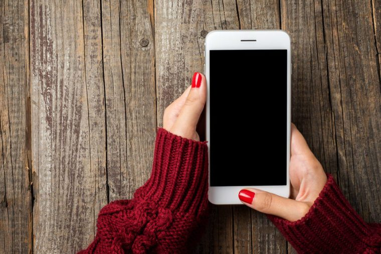 Female hands in warm sweater holding white smart phone
