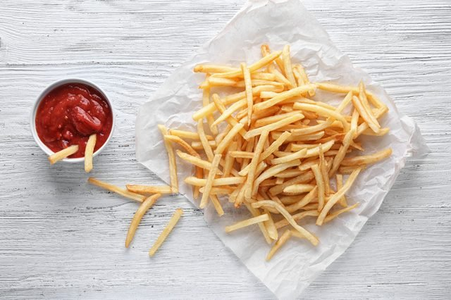 Yummy french fries and sauce in small bowl on wooden background