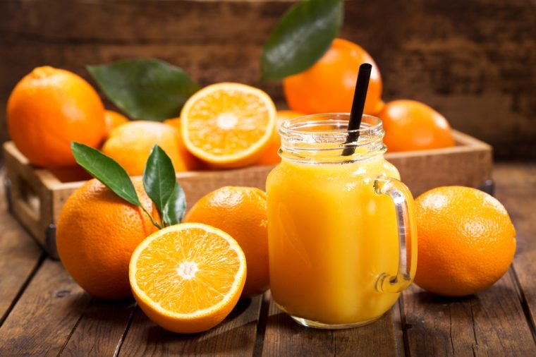 glass jar of fresh orange juice with fresh fruits on wooden table