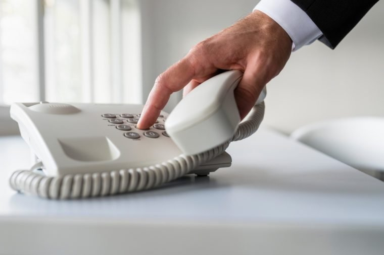 Male hand dialing a telephone number in order to make a phone call on a classical white landline telephone on an office desk.