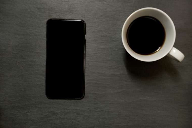 Mobile phone/ smart phone and cup of coffee - from above on dark slate table top background, with copy space