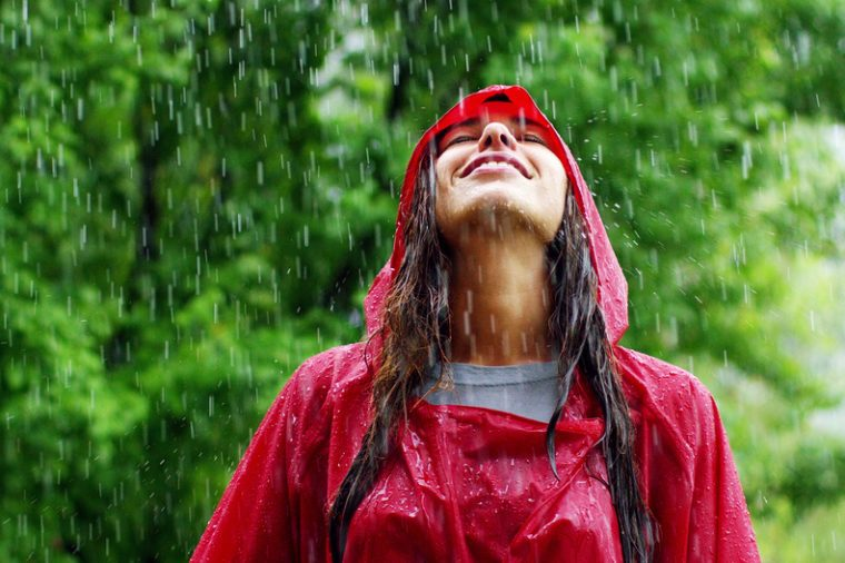 girl smiles, spins and laughs in the rain. the rain falls, the drops fall on his face and the girl is happy with life and nature around. concept of nature and happy life. Adventure, purity.