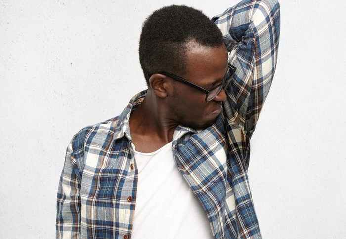 Disgusted young male wearing checkered shirt and glasses smelling wet sweaty armpit after stressful meeting, feeling nauseous, screwing lips. Black man can't stand bad smell. Hyperhidrosis and hygiene