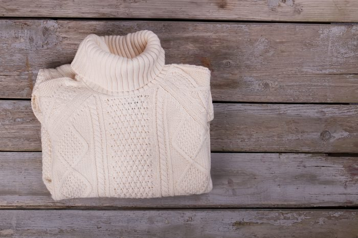 White roll neck sweater folded on wooden background. Beautiful patterns and quality woolen yarn. Fall and winter clothes.