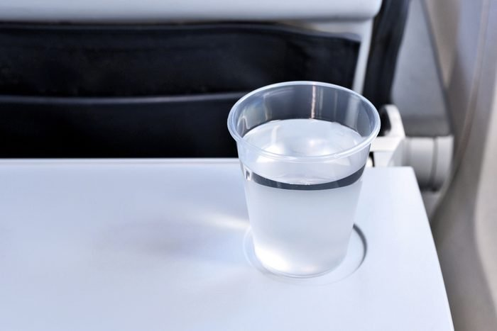 Cup or glass of water on a flight. Travel by plane, table with drink.