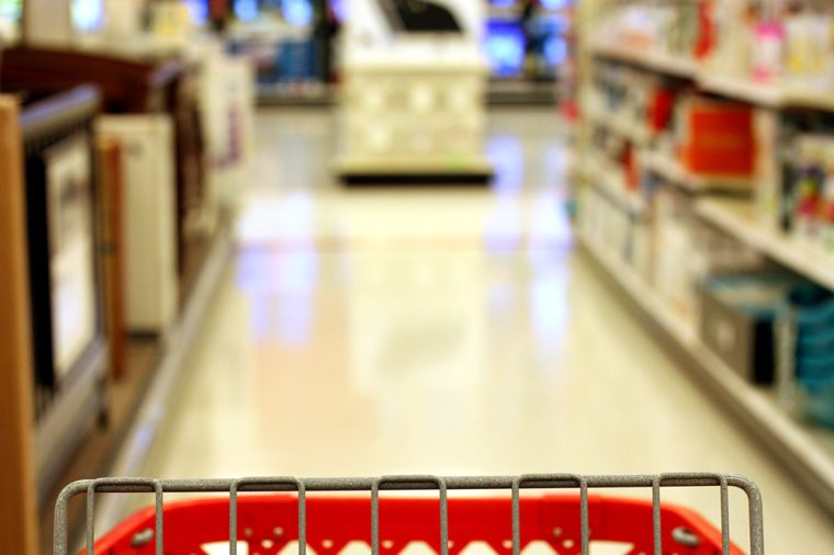 Red shopping cart in store aisle