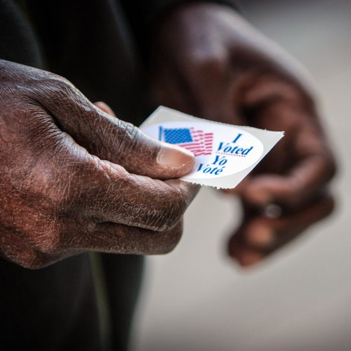 """An elderly African American man holds his """"I voted"""" sticker after he cast his ballot in Washington, DC."""