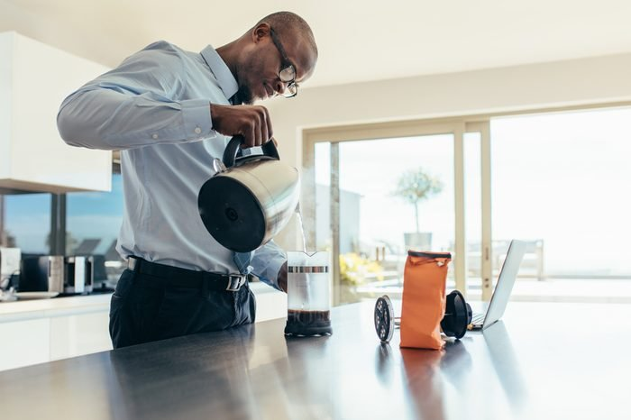 Man pouring hot water in coffee maker. Businessman preparing coffee on breakfast table with a laptop computer by the side.