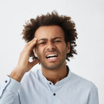 Picture of stressed young unshaven Afro-American employee in formal shirt having painful look, touching his head because of bad headache or migraine after he worked all day in office. Body language