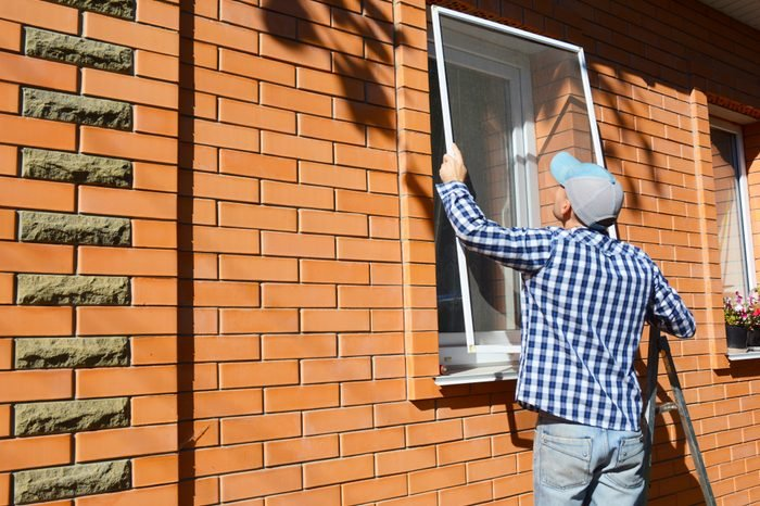 Worker installing mosquito net or mosquito wire screen on brick house window.