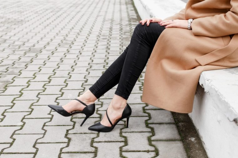 Women's legs in black high heel shoes and black jeans in the city street. Trendy elegant casual outfit. Details of everyday look. Street fashion.