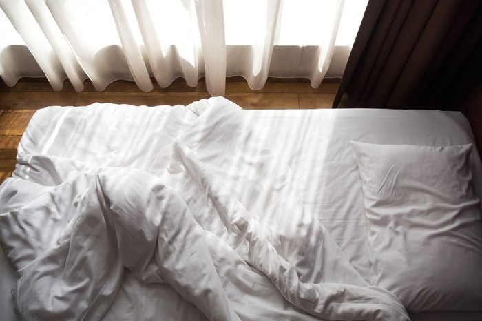Messy bed. White pillow and blanket with sunlight through window. Relaxing concept. Unmade bed.