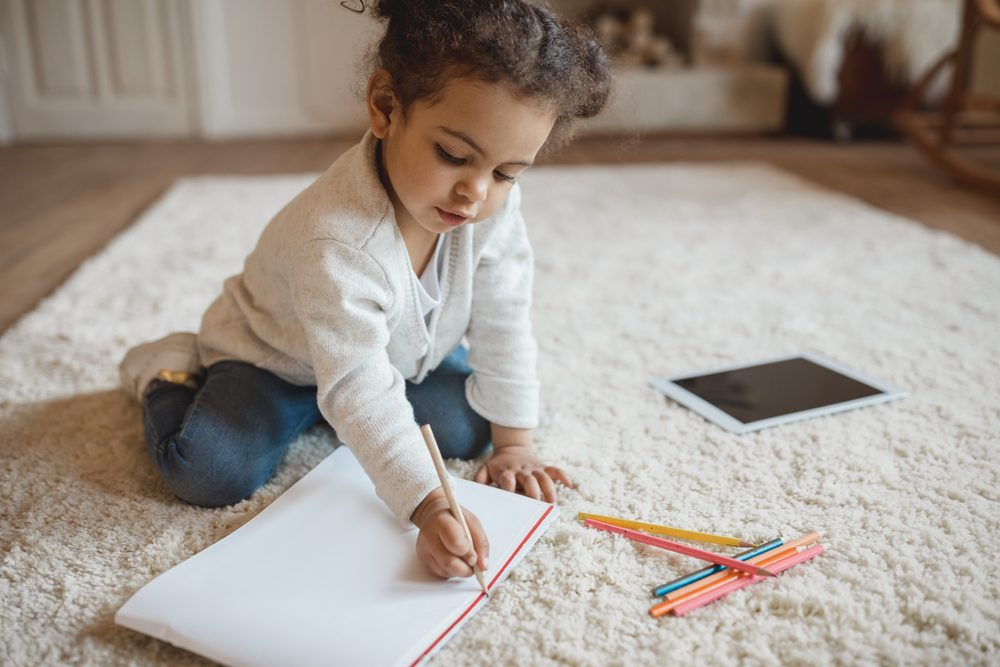 adorable little african american girl drawing with pencils and lying on carpet at home