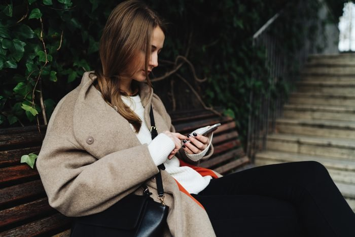 Portrait of blonde caucasian woman wearing trendy clothes holding mobile phone while sitting on a natural background. Student girl is surfing the web on a smartphone while relaxing in park.