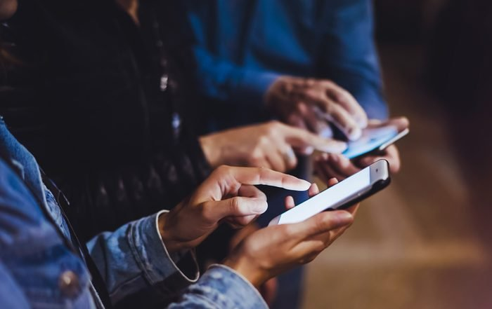 Bloggers together pointing finger on screen smartphone on bokeh light in night atmospheric city, group adult hipsters friends using in hands mobile phone closeup, street online wi-fi internet concept