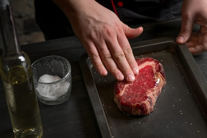 Chef hands cooking steak in the kitchen on the classic recipe on the grill pan. Cook on a dark background for text or design, horizontal photo.