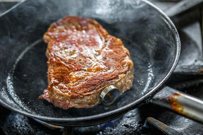Grilled pork steak with meat thermometer in a frying pan