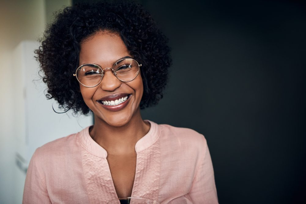 Young African businesswoman wearing glasses and laughing while standing alone in a modern office