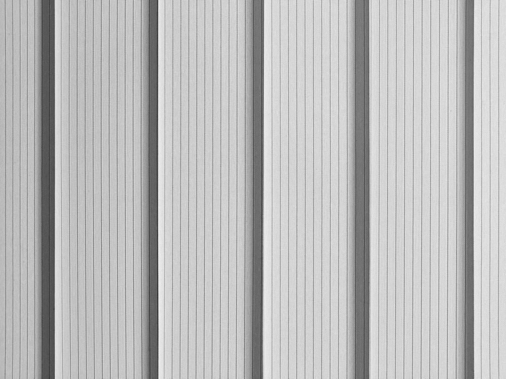 Background vertical office light blinds in backlight. Black and white monochrome image