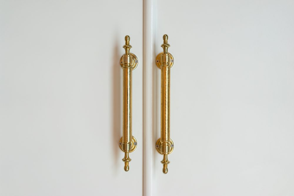 Brass handles with white doors