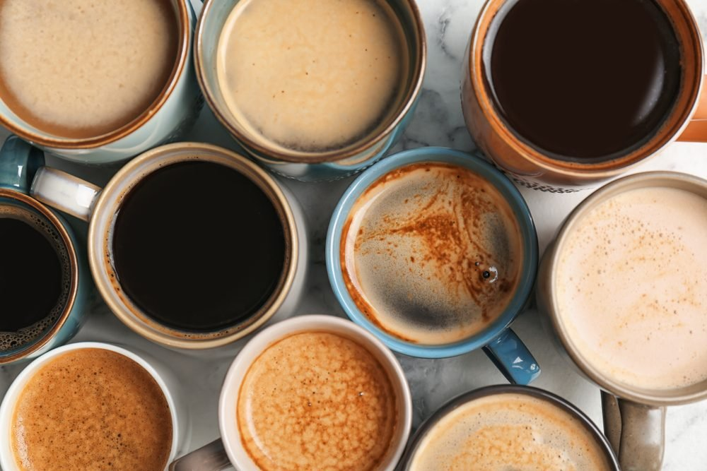 Many cups of different aromatic hot coffee on table, top view