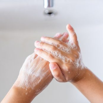 Hygiene concept. Kid washing hands with soap.