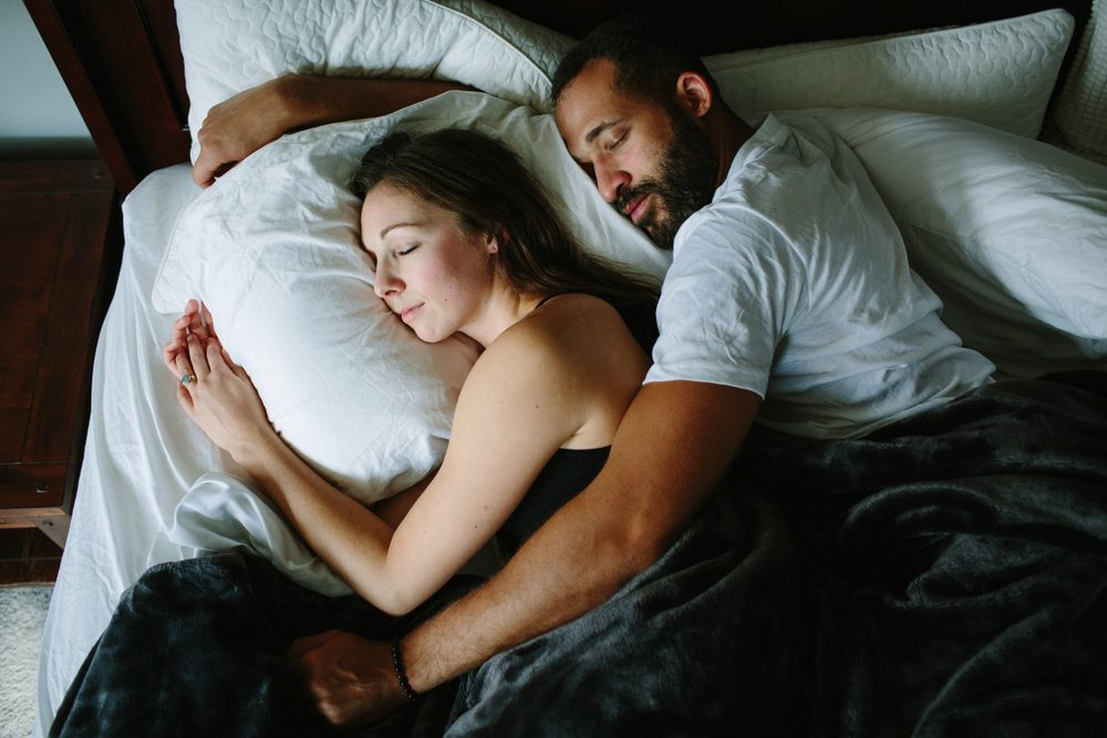 Black and white couple sleeping and holding each other in bed