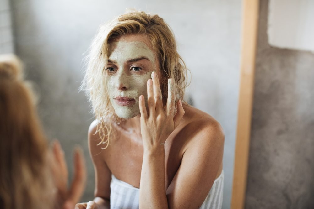 Beautiful blonde Caucasian woman standing in her bathroom and putting cosmetic mask on her face.