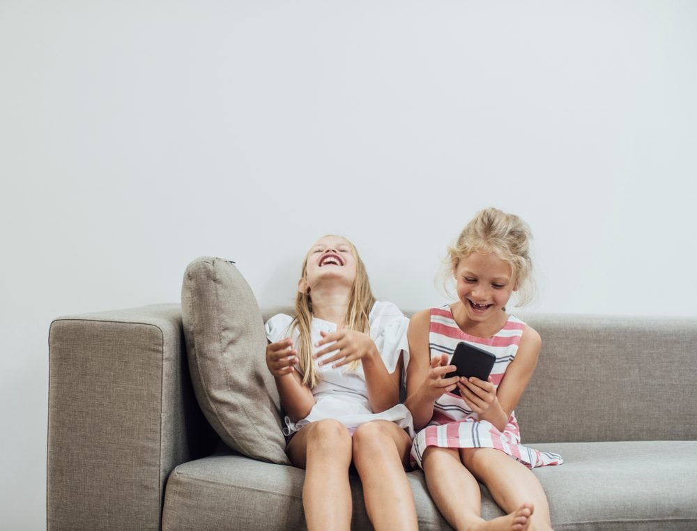 Two cute Caucasian blonde girls sisters holding cell phone and laughing.