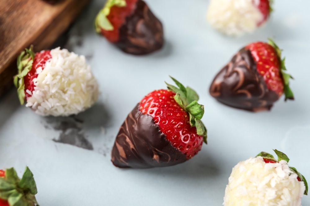 Delicious strawberries covered with chocolate on color background